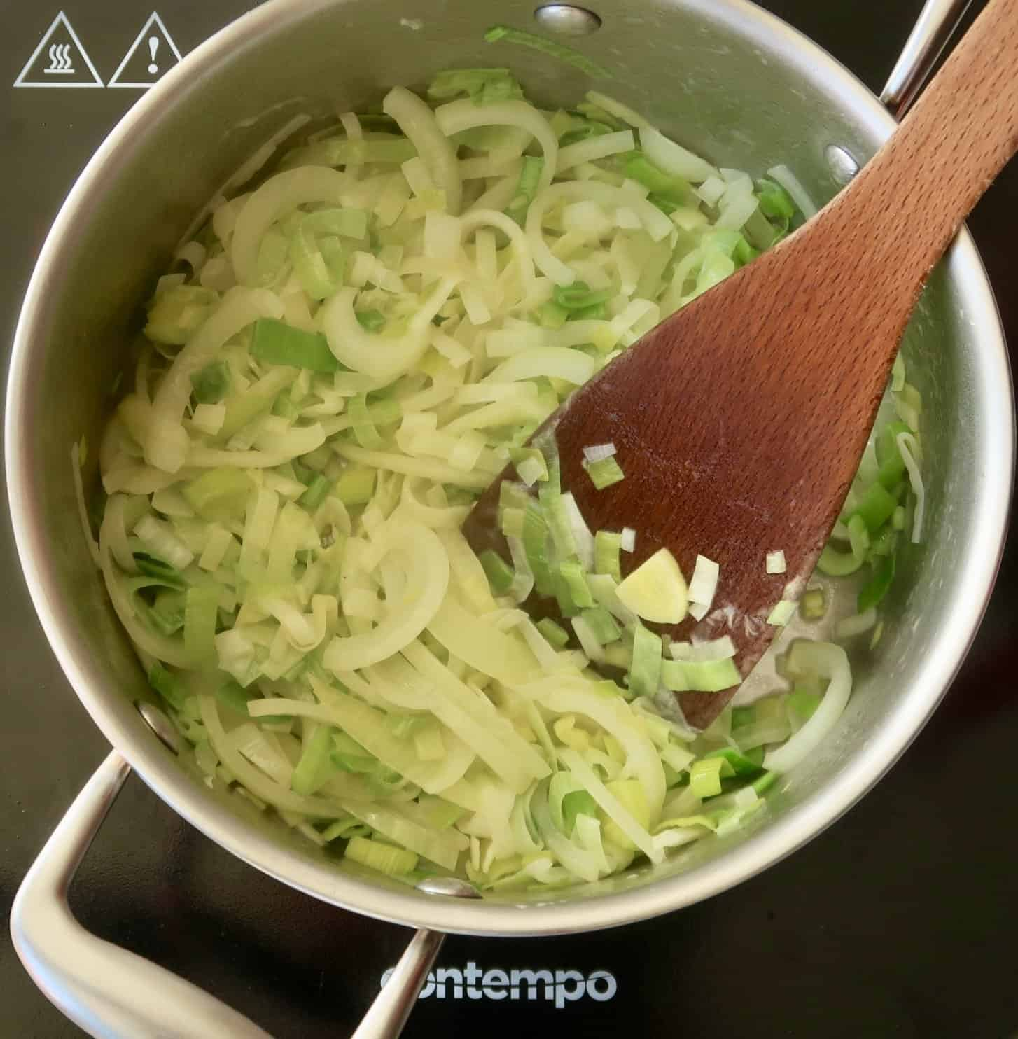 leeks and onions in a silver saucepan with a wooden spoon