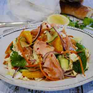 chilli caramel salmon salad completed and served on a white plate with black border