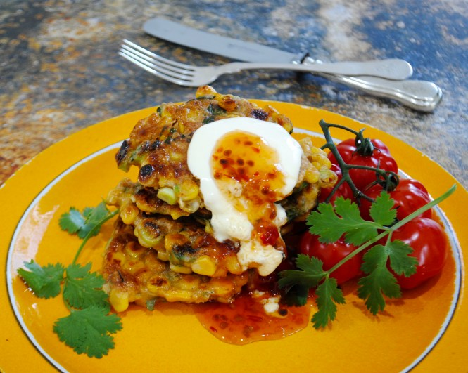 sweet corn fritters served on an orange plate with three fritters stacked sour cream and sweet chilli sauce cherry tomatoes on the vine and coriander garnish