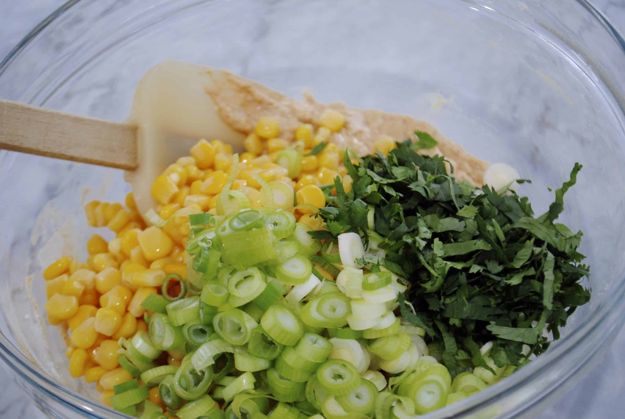 sweet corn fritters batter with corn, coriander and shallots added with a spatula