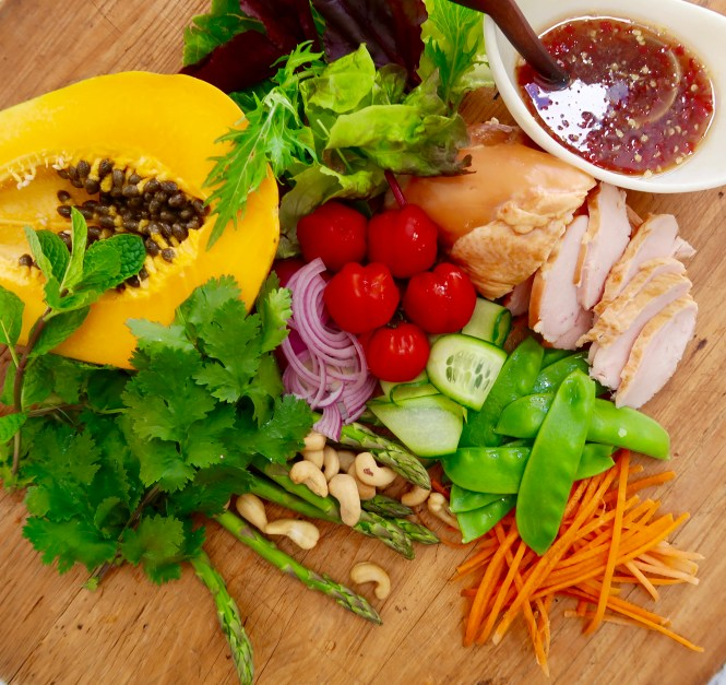 thai smoked chicken and papaya salad ingredients on a wooden chopping board