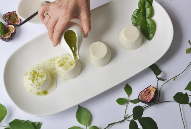 Coconut and lime panna cotta on a white plate being dressed with a lime syrup