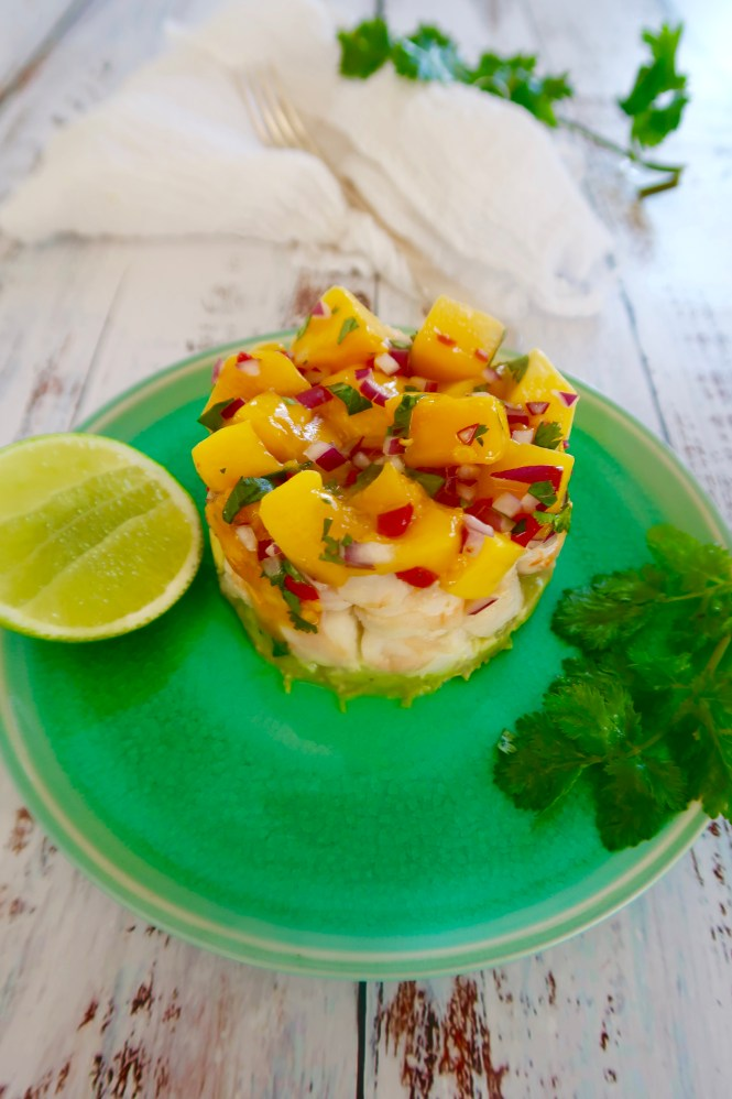 asian prawn, mango and avocado cocktail stack served on a green plate with lime cheek and coriander garnish