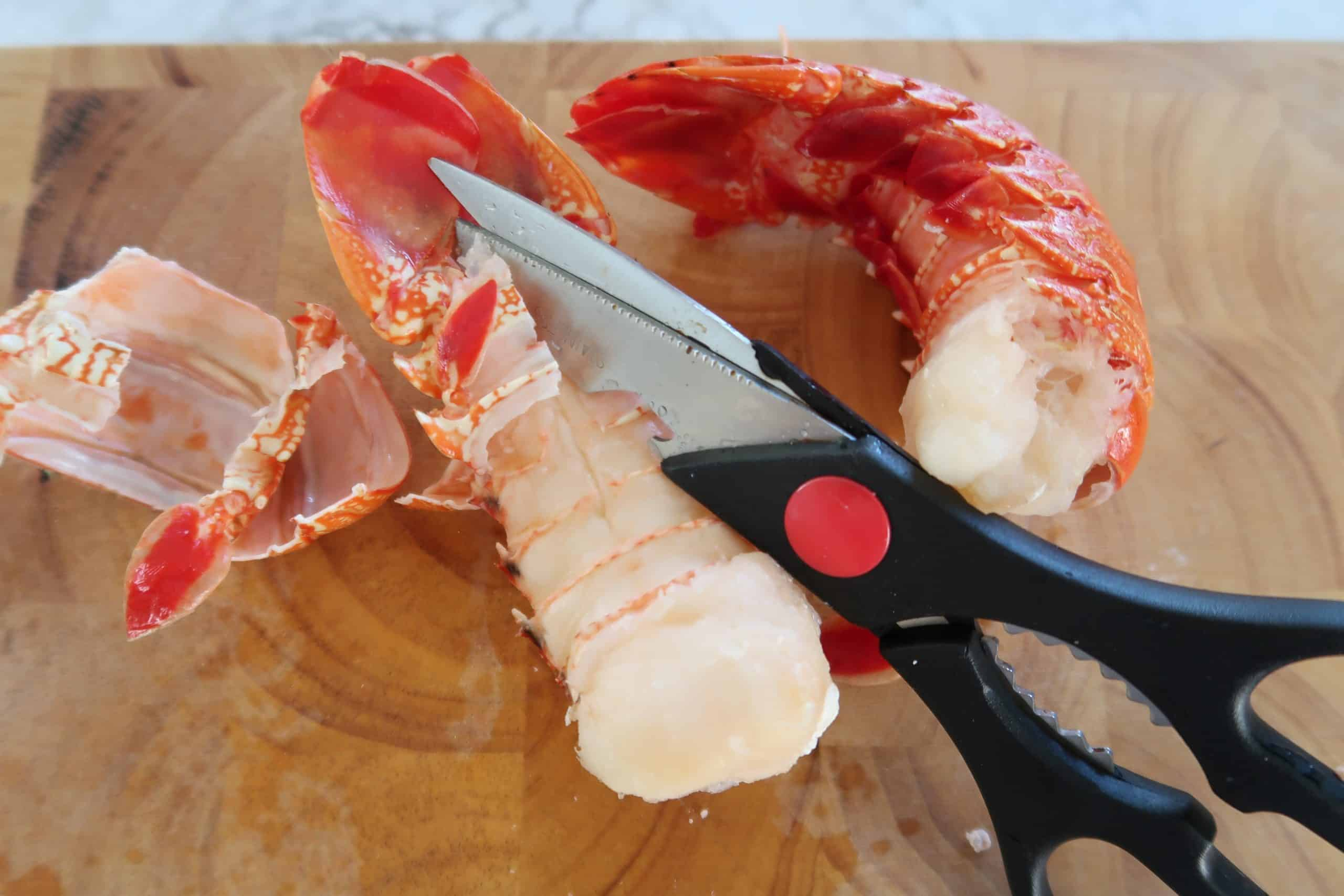 thai mango and lobster salad showing two lobster tails and kitchen scissors cutting down the length of the shell to remove shell