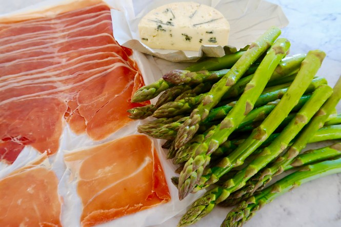 asparagus with prosciutto and blue cheese ingredients laid out on kitchen bench ready to roll