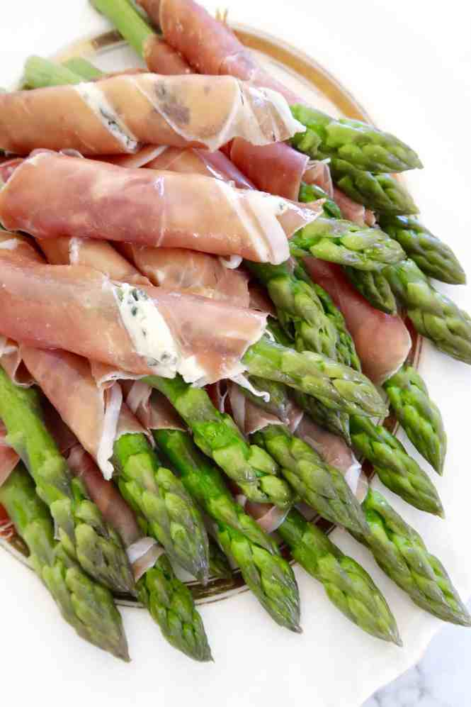 asparagus with prosciutto and blue cheese bundled on a white plate ready to serve