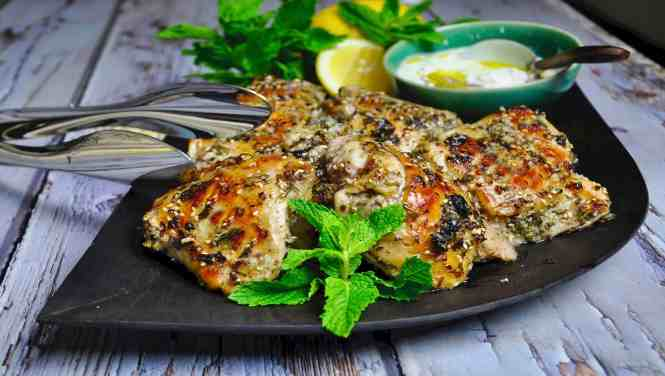Middle Eastern Herb and Garlic Chicken Thighs on a wooden platter with silver tongs