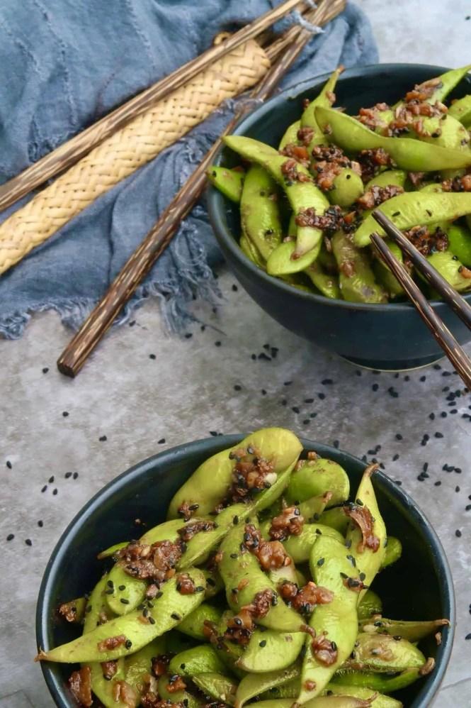 garlic chilli edamame served in two black bowls with chopsticks