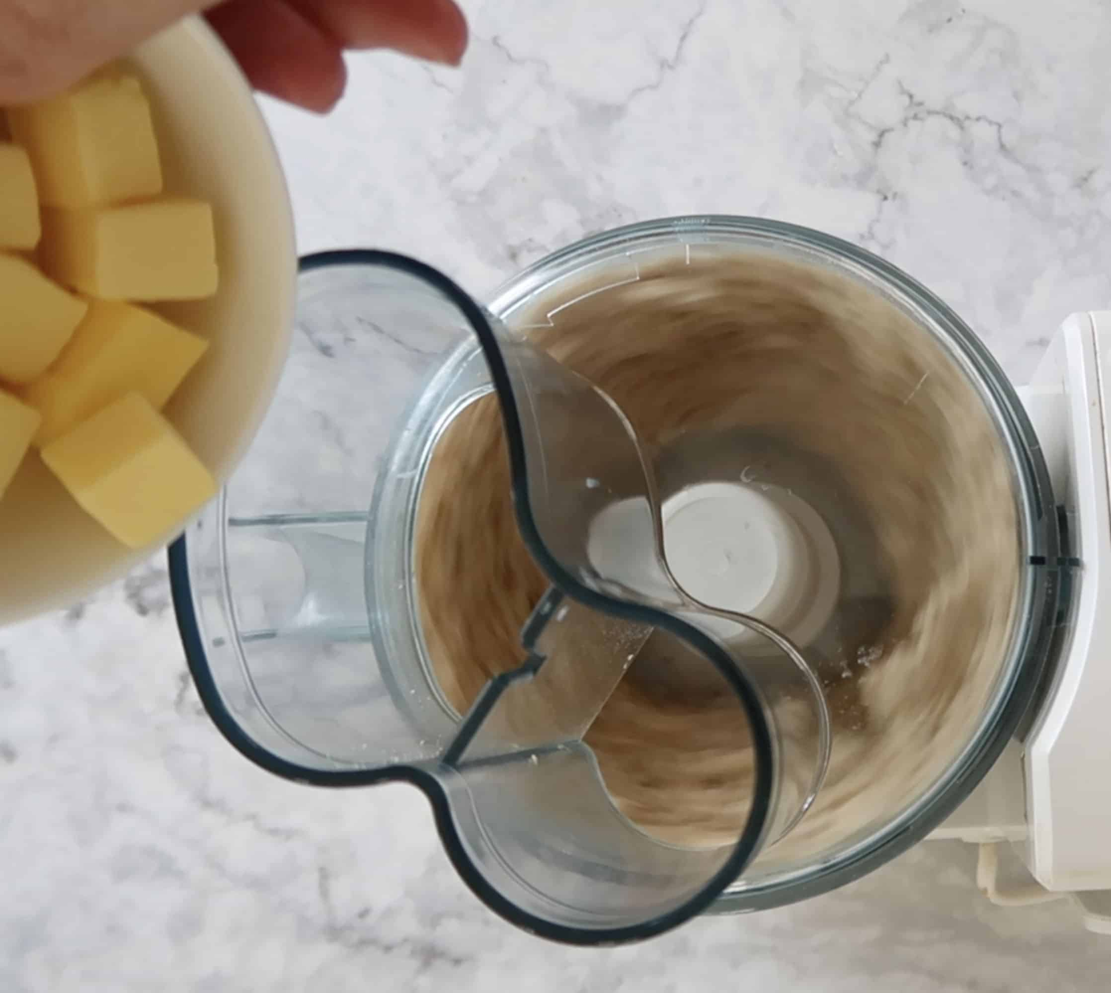 adding butter to a blender to make Anchovy, Cheese and Pine Nut Biscuits