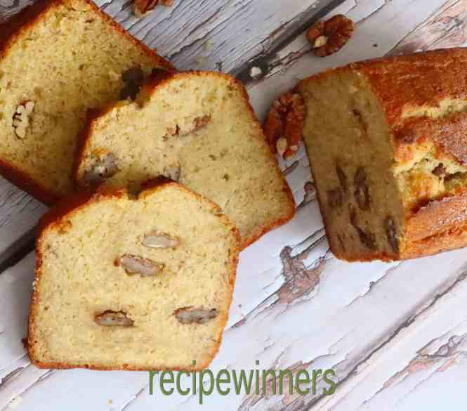Banana and Pecan Bread on a timber table with pecan nuts scattered around