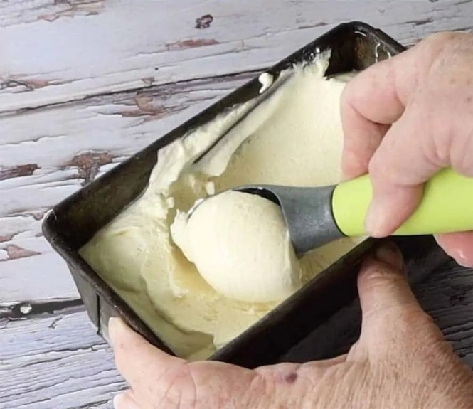 no churn vanilla bean ice cream being scooped with a green handled ice cream scoop