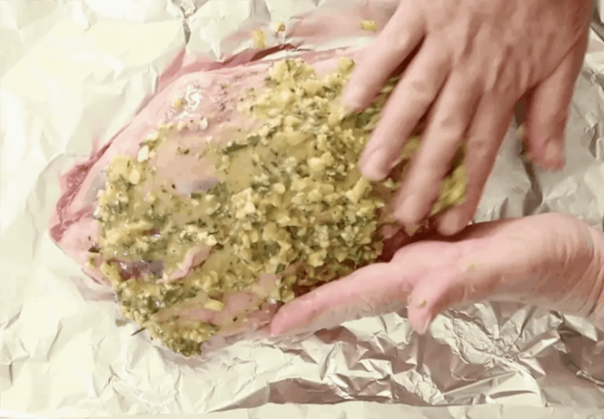 massaging lemon and herbs into lamb shoulder to make Slow Roasted Greek Shoulder of Lamb