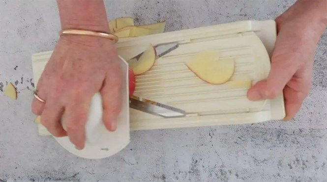 Thinly sliced potatoes on a concrete table with a mandoline