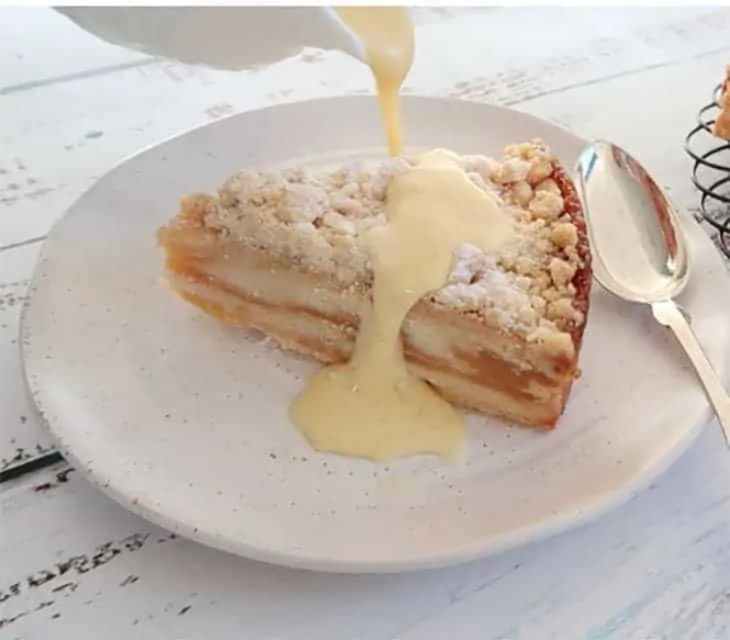 a slice of apple cake with Super Simple Creme Anglaise being poured from a jug