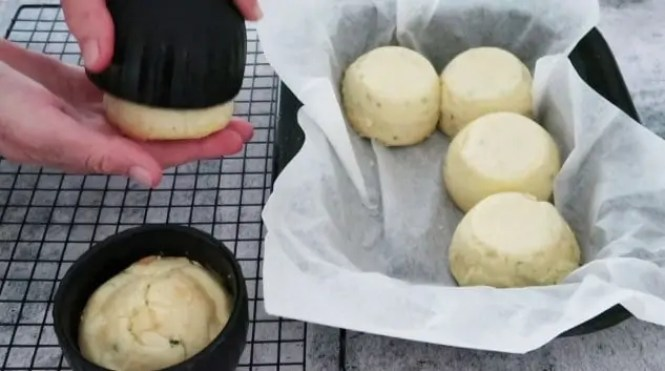 turning out Easy Twice Baked Cheese Souffles into a lined baking dish