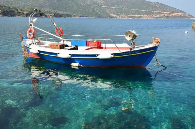 Bateau de pêcheur flottant sur l'eau translucide de Kyparissi, Grèce