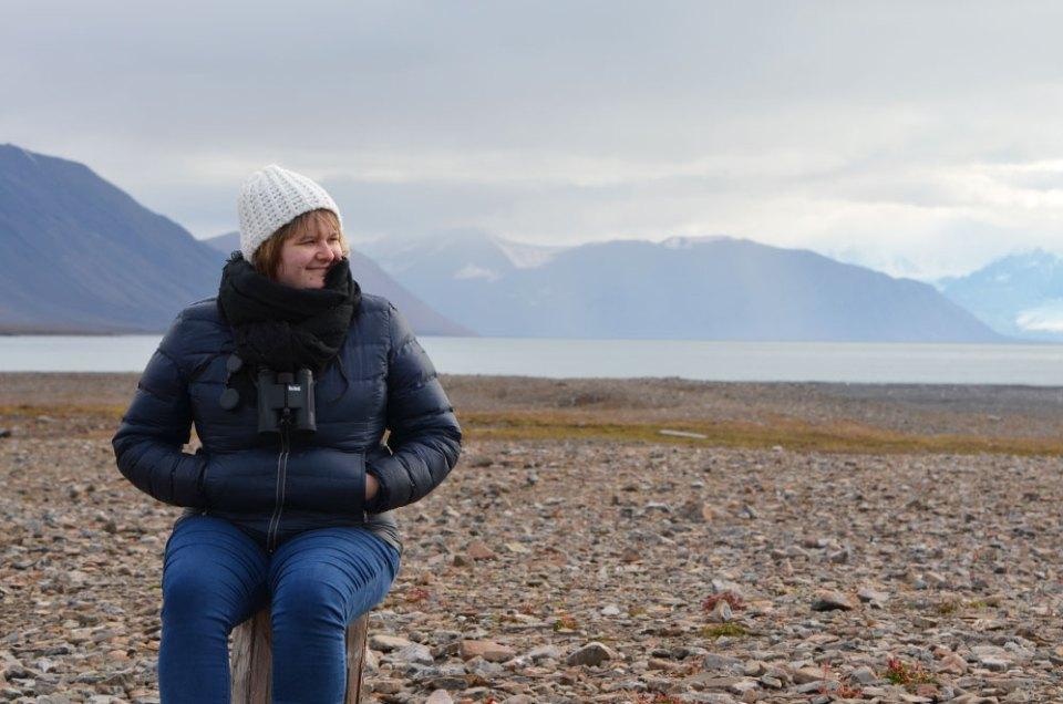 Marie-Catherine assise sur un rondin de bois lors d'une randonnée au Svalbard