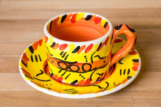 Abstract small cup and saucer in yellow