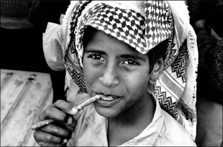 A young Saudi boy cleaning his teeth with miswak