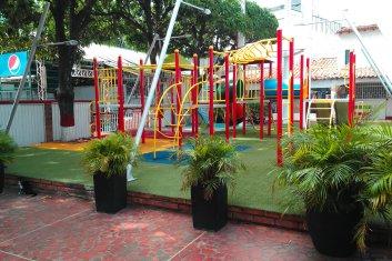 Der knallbunte Spielplatz - nein, auch hier kein Gras, sondern komischer Plastikrasen.