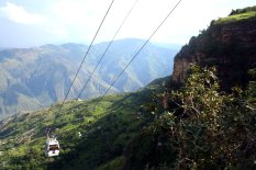 Rechts der Schwebebahn erheben sich riesige Berge, und die Häuser verschwinden fast zwergengleich.