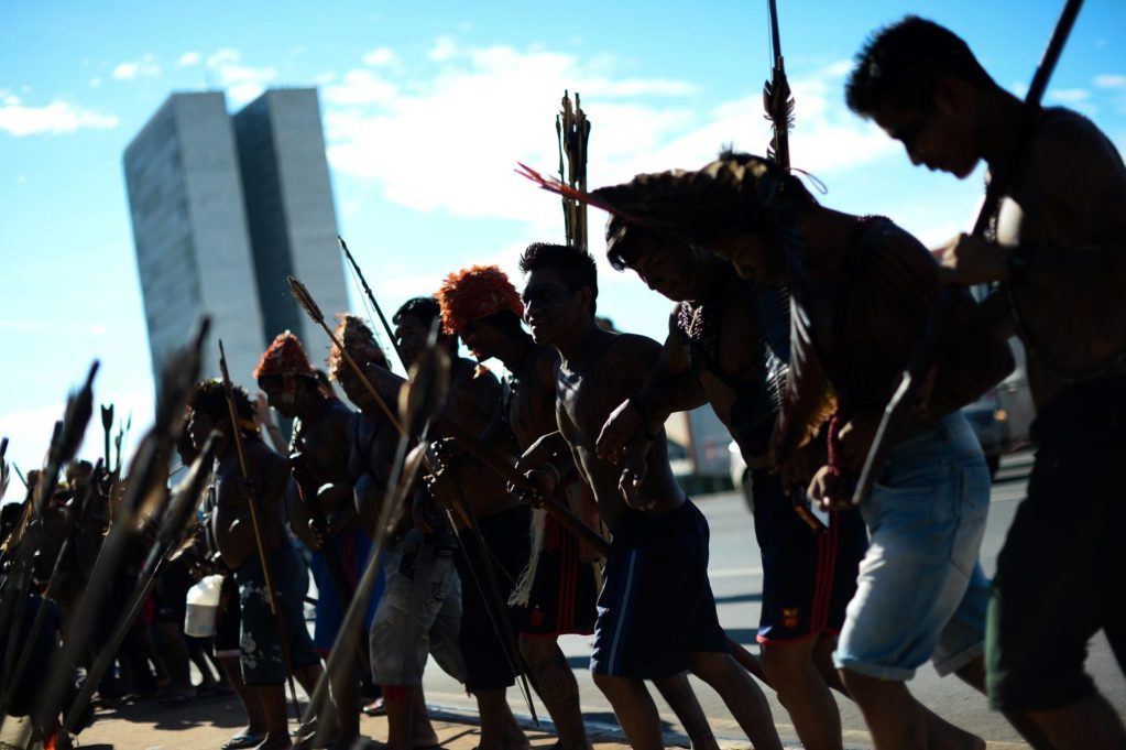 Citizens lock arms in a line and walk forward together.