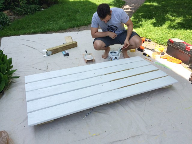 Reconnect Rochester volunteers painting the bench top.