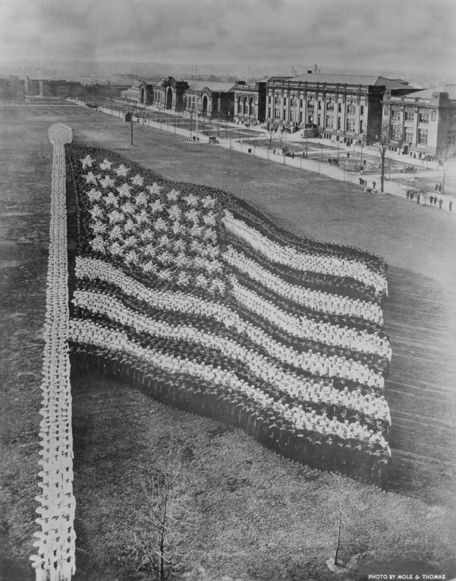 Living photograph of an American flag comprised of 10,000 recruits at the Great Lakes Naval Training Station, Illinois, June 11, 1917. Width of left side of the flag: 428 feet; width of the right side of the flag: 128 feet; length of top of the flag: 293 feet; length of bottom of the flag: 73 feet; width of left end of star field: 350 feet; width of right end of star field: 184 feet; length of top of star field: 143 feet; length of bottom of star field: 66 feet. 700 men were used to form the flagpole. The star on the lower right side used twelve men, while the star on the upper right side required sixty-five. (Photo by Arthur S Mole & John D Thomas/Chicago History Museum/Getty Images)