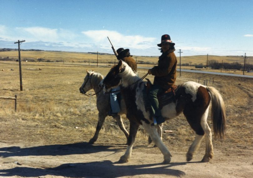 Two armed members of the American Indian Movement (AIM) on horseback patrol along a street during their occupation of the town of Wounded Knee on the Pine Ridge Reservation, South Dakota, 1973. AIM occupied the town, exchanging gunfire with local and federal troops, from February 27 through May 8, 1973, following internal reservation disputes as well as disatisfaction with the US government's treatment of Native American peoples in general. (Photo by Peter Davis/Getty Images)