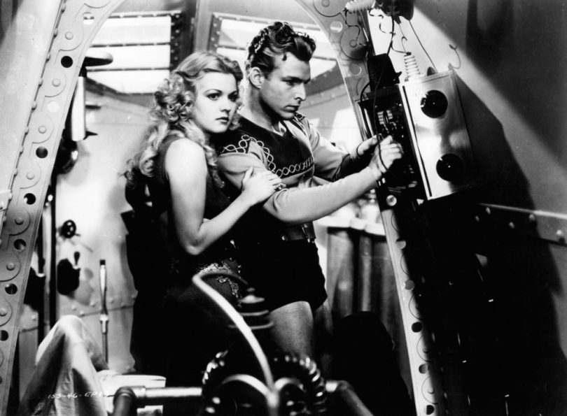 Jean Rogers holding onto Buster Crabbe in a scene from the film 'Flash Gordon', 1936. (Photo by Universal/Getty Images)