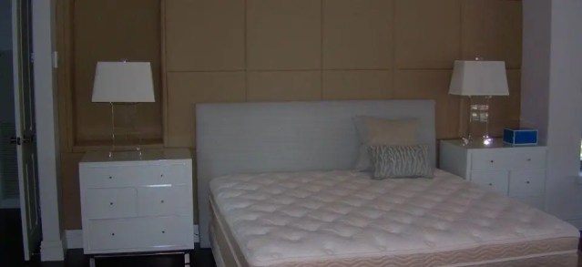 Custom padded wall panel installation behind upholstered headboard