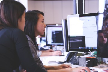 Reducing high staff turnover - two motivated employees looking at a computer screen