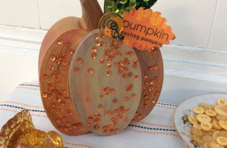 Decorate a pumpkin with sequins and buttons