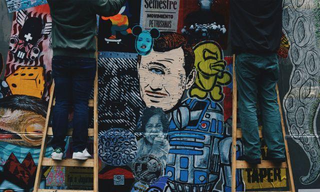 Gerdy trabajando con un compañero de BA Paste Up para crear un mural.