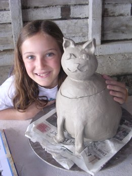 My younger daughter with her clay creation at clay camp.  It lives in our kitchen and holds yummy things.