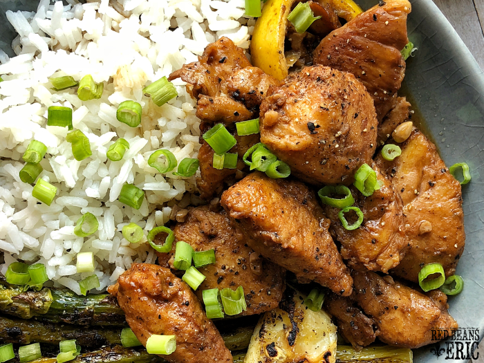 A plate of Eric's New Orleans style Barbeque Chicken with white rice topped with chopped green onions