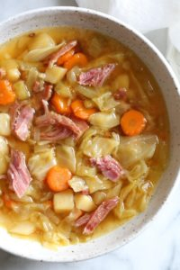 A bowl of ham bone soup with potatoes and cabbage