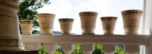 guy wolff white pots on a porch rail