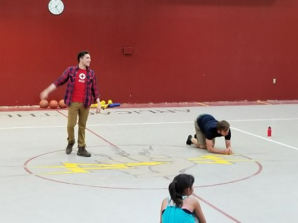 Red Cross Preparedness Specialist Steven Fisher plays a game of Disaster Simon Says with a Campfire counselor and children
