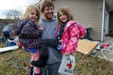 Missouri Floods. Jason Gallagher holds his two daughters, Cassidy (left), 3, and Adilyn (right), 4, during the flood relief effort in Arnold, Missouri. Photo by Daniel Cima for the American Red Cross