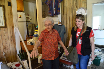 Daurline Tanner shoes a Red Cross worker around her damaged home