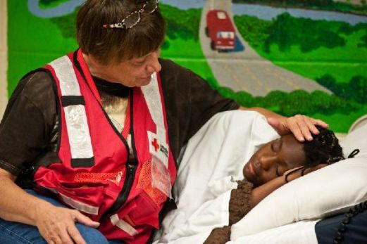 July 10, 2012. Martin Luther King Community Center, Charleston, West Virginia. Red Cross nurse Vicki Gurriell comforts 10-year-old Unique Lloyd who has an ear infection. For the past nine days, Unique and her family have been staying at the Red Cross shelter since their home lost power and the water was shut off after powerful storms struck their neighborhood. Photo by Daniel Cima/American Red Cross