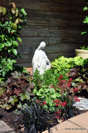 Coral bells and variegated Hostas surround Mary