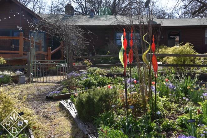 Back garden with the sunlight glowing through blown glass art.