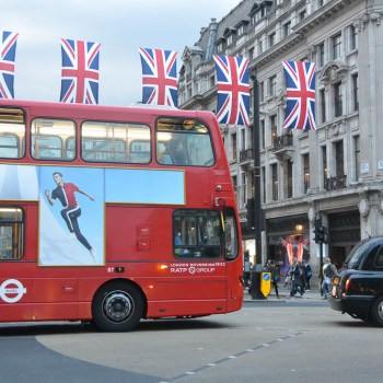 Red double-decker bus and London cab with the Union Jack flying overhead.