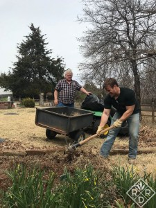Brennan using a pick mattock to break up the Bermuda grass and compacted soil.