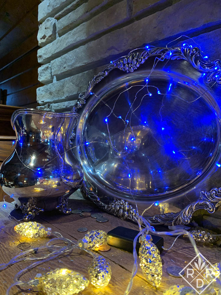 Silver platter and water pitcher with blue and white lights.