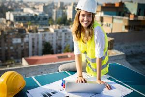 Young female construction specialist engineer reviewing blueprints at construction site