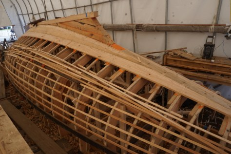 planking continues from the keel down until the planks run full length to the transom. At that point the sheer plank is installed and planking is completed from the bottom up as well to improve efficiency.