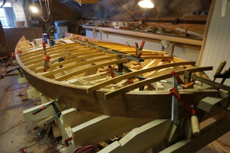 The house is assembeled on the lofting floor to allow for varnishing in the warmth of the shop while the rest of the hull's interior is built and the deck is put down. Here the last few house beams are being fit and faired.